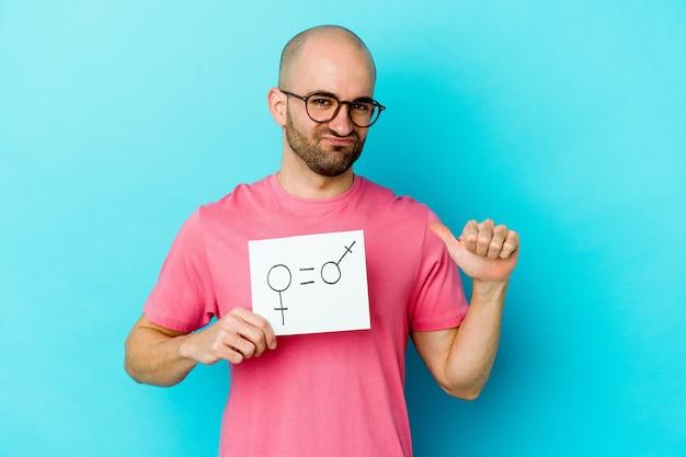 Junger kaukasischer kahlköpfiger mann, der ein gleichheitsgeschlechtsplakat lokalisiert auf gelber wand hält, fühlt sich stolz und selbstbewusst, beispiel zu folgen.