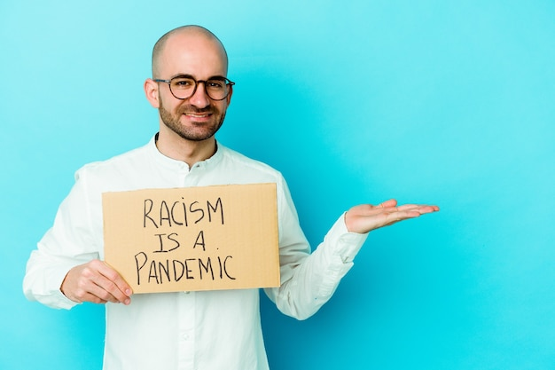 Junger kaukasischer kahlköpfiger mann, der einen rassismus hält, ist eine pandemie auf weiß, die einen kopienraum auf einer handfläche zeigt und eine andere hand auf taille hält.