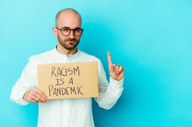 Junger kaukasischer kahlköpfiger mann, der einen rassismus hält, ist eine pandemie, die auf weißer wand isoliert ist und nummer eins mit finger zeigt.
