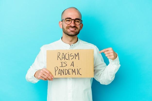 Junger kaukasischer kahlköpfiger mann, der einen rassismus hält, ist eine pandemie isoliert auf weißer wandperson, die von hand auf einen hemdkopierraum zeigt, stolz und zuversichtlich