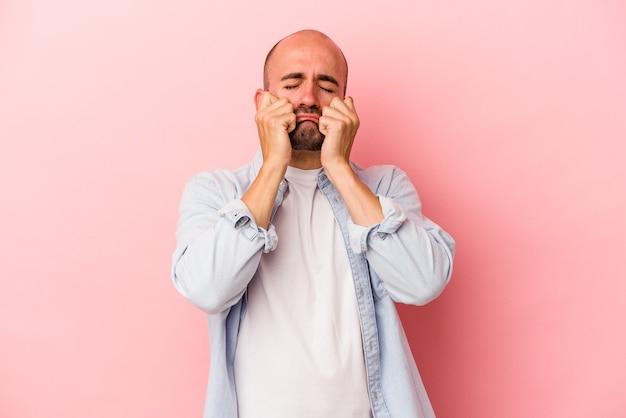 Junger kaukasischer kahlköpfiger mann einzeln auf rosafarbenem hintergrund, der untröstlich jammert und weint.