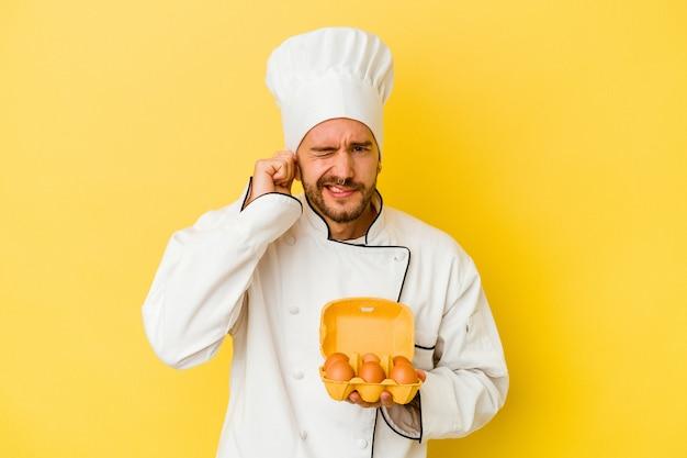 Junger kaukasischer kochmann, der eier lokalisiert auf gelbem hintergrund hält, der ohren mit händen bedeckt.