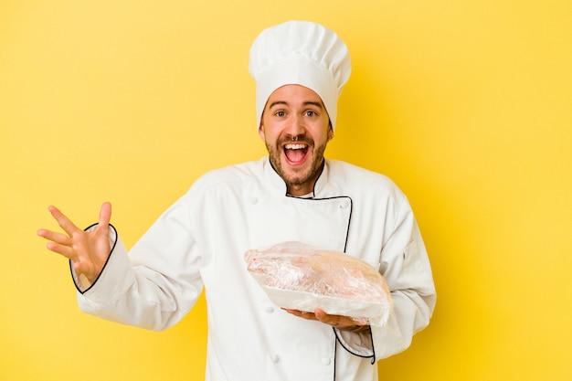 Junger kaukasischer kochmann, der huhn lokalisiert auf gelbem hintergrund hält, der eine angenehme überraschung empfängt, aufgeregt und hände erhebt.