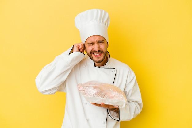 Junger kaukasischer kochmann, der huhn lokalisiert auf gelbem hintergrund hält, der ohren mit händen bedeckt.