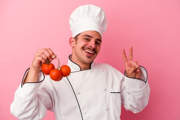Junger kaukasischer kochmann, der tomaten einzeln auf rosafarbenem hintergrund hält, freudig und sorglos, der ein friedenssymbol mit den fingern zeigt.