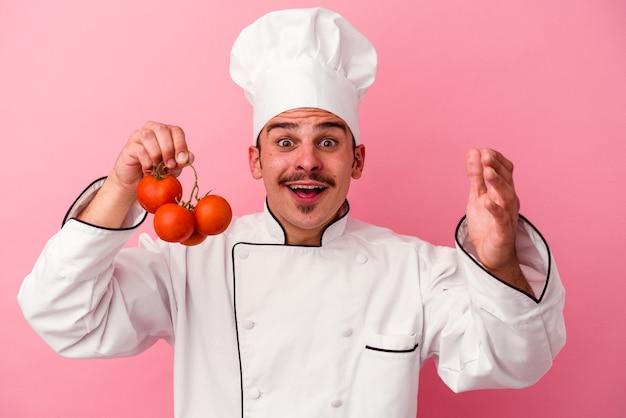 Junger kaukasischer kochmann, der tomaten einzeln auf rosafarbenem hintergrund hält und eine angenehme überraschung empfängt, aufgeregt und die hände hebt.