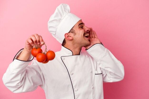 Junger kaukasischer kochmann, der tomaten einzeln auf rosafarbenem hintergrund hält und palme nahe geöffnetem mund schreit und hält.