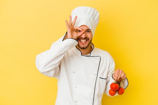 Junger kaukasischer kochmann, der tomaten lokalisiert auf gelbem hintergrund aufgeregt hält, ok geste auf auge halten.