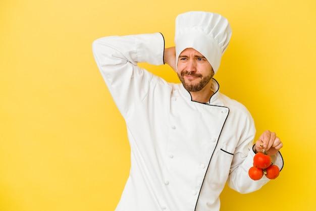 Junger kaukasischer kochmann, der tomaten lokalisiert auf gelbem hintergrund hält, der hinterkopf berührt, denkt und eine wahl trifft.