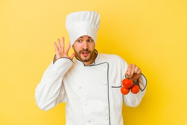Junger kaukasischer kochmann, der tomaten lokalisiert auf gelbem hintergrund hält, der versucht, einen klatsch zu hören.