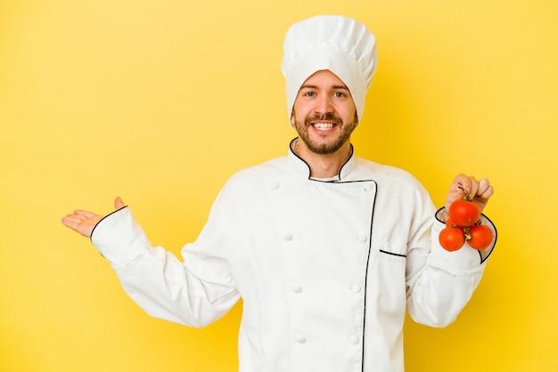 Junger kaukasischer kochmann, der tomaten lokalisiert auf gelbem hintergrund zeigt, der einen kopienraum auf einer handfläche zeigt und eine andere hand auf taille hält.