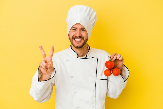 Junger kaukasischer kochmann, der tomaten lokalisiert auf gelbem hintergrund zeigt, der nummer zwei mit fingern zeigt.