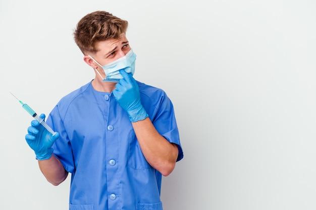 Junger kaukasischer krankenschwestermann, der bereit war, einen impfstoff einzeln auf weißem hintergrund zu geben, entspannte sich beim nachdenken über etwas, das einen kopierraum betrachtet