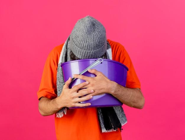 Junger kaukasischer kranker mann, der brille wintermütze und schal hält plastikeimer mit übelkeit erbrechen in eimer lokalisiert auf purpurroter wand