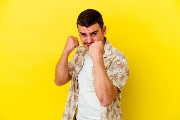 Junger kaukasischer kühler mann lokalisiert auf gelber wand, die faust, aggressiven gesichtsausdruck zeigt.