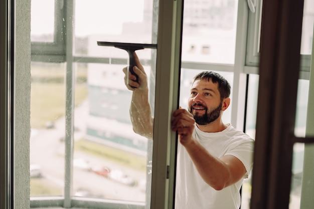 Junger kaukasischer lächelnder mann, der das fenster mit einem rakel wäschtreinigungskonzept