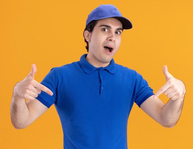 Junger kaukasischer lieferbote in blauer uniform und mütze