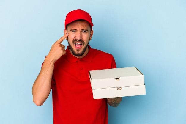 Junger kaukasischer lieferbote mit tätowierungen, die pizzas einzeln auf blauem hintergrund halten, die eine enttäuschungsgeste mit dem zeigefinger zeigen.