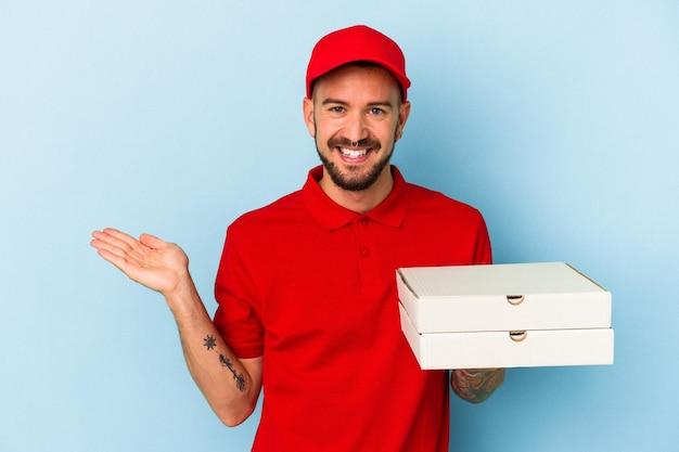 Junger kaukasischer lieferbote mit tätowierungen, die pizzas einzeln auf blauem hintergrund halten, die einen kopienraum auf einer handfläche zeigen und eine andere hand an der taille halten.