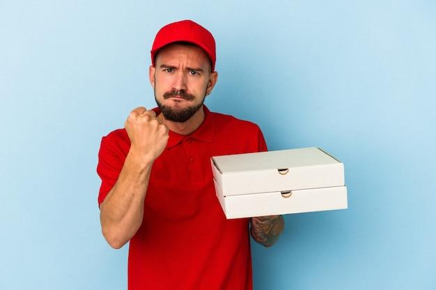 Junger kaukasischer lieferbote mit tätowierungen, die pizzas einzeln auf blauem hintergrund halten, die faust zur kamera zeigen, aggressiver gesichtsausdruck.