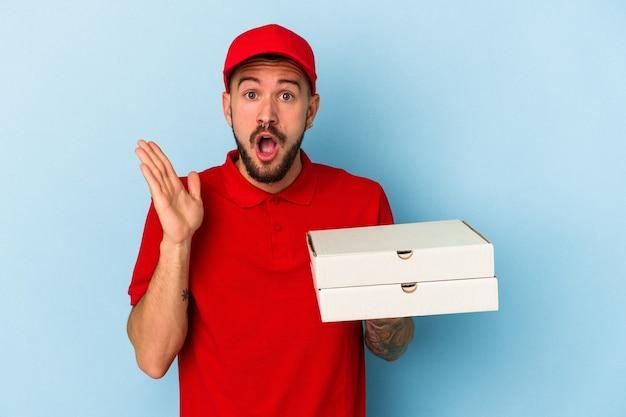 Junger kaukasischer lieferbote mit tätowierungen, die pizzas einzeln auf blauem hintergrund halten überrascht und schockiert.
