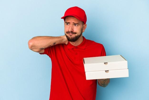 Junger kaukasischer liefermann mit tätowierungen, der pizzas einzeln auf blauem hintergrund hält, der den hinterkopf berührt, denkt und eine wahl trifft.
