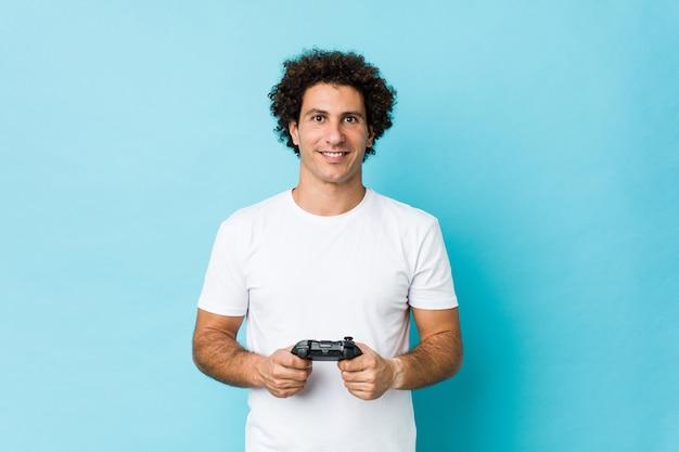 Junger kaukasischer lockiger mann, der einen spielcontroller glücklich, lächelnd und fröhlich hält.