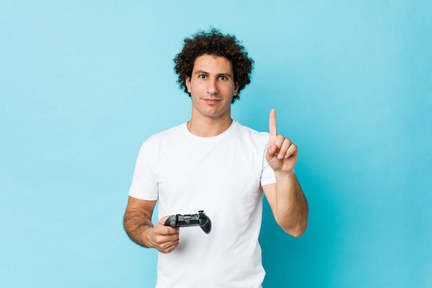 Junger kaukasischer lockiger mann, der einen spielcontroller hält, der nummer eins mit finger zeigt.