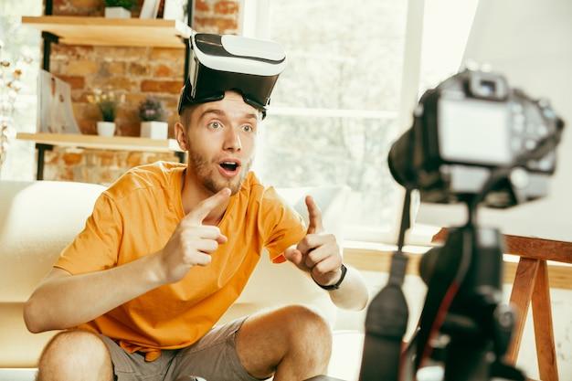Junger kaukasischer männlicher blogger mit professioneller ausrüstung, die videoüberprüfung der vr-brille aufzeichnet
