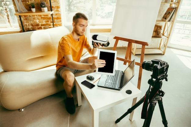 Junger kaukasischer männlicher blogger mit professioneller ausrüstung, die videoüberprüfung der vr-brille zu hause aufzeichnet