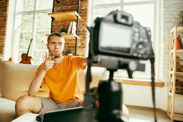 Junger kaukasischer männlicher blogger mit professioneller kameraaufzeichnung videoüberprüfung von gadgets zu hause