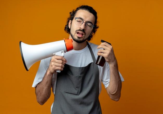 Junger kaukasischer männlicher friseur, der brille und welliges haarband im einheitlichen haltelautsprecher und in der sprühflasche mit geschlossenen augen trägt, lokalisiert auf orange hintergrund mit kopienraum