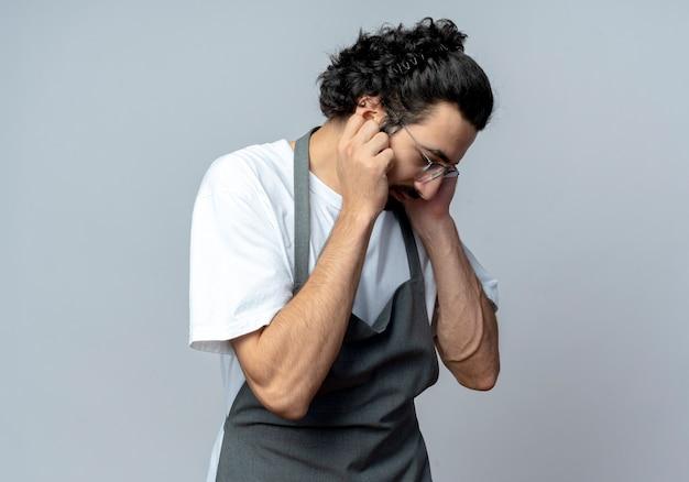 Junger kaukasischer männlicher friseur, der brille und welliges haarband in uniform trägt, die am telefon sprechen, das unten schaut und gesicht berührt, das auf weißem hintergrund mit kopienraum lokalisiert wird