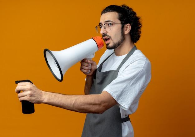 Junger kaukasischer männlicher friseur, der brille und welliges haarband in uniform trägt, die in der profilansicht hält, die sprühflasche hält und durch sprecher spricht, der gerade lokalisiert auf orange hintergrund schaut