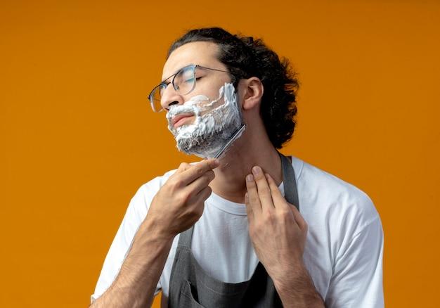 Junger kaukasischer männlicher friseur, der eine brille und ein welliges haarband in uniform trägt, der seinen eigenen bart mit einem rasiermesser rasiert, mit rasierschaum auf seinem gesicht liegt und seinen hals mit geschlossenen augen berührt