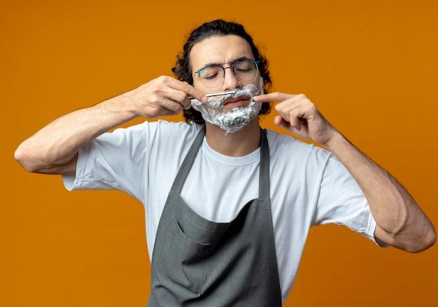 Junger kaukasischer männlicher friseur, der eine brille und ein welliges haarband in uniform trägt, der seinen schnurrbart mit einem rasiermesser rasiert, mit rasierschaum auf seinem gesicht und auf rasiermesser zeigt