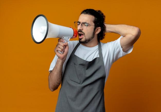 Junger kaukasischer männlicher friseur, der uniform und brille trägt, die in lautsprecher mit geschlossenen augen und hand hinter kopf schreien, lokalisiert auf orange hintergrund