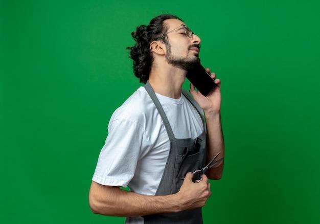 Junger kaukasischer männlicher friseur mit brille und welligem haarband in uniform, der am telefon spricht und eine schere mit geschlossenen augen hält holding