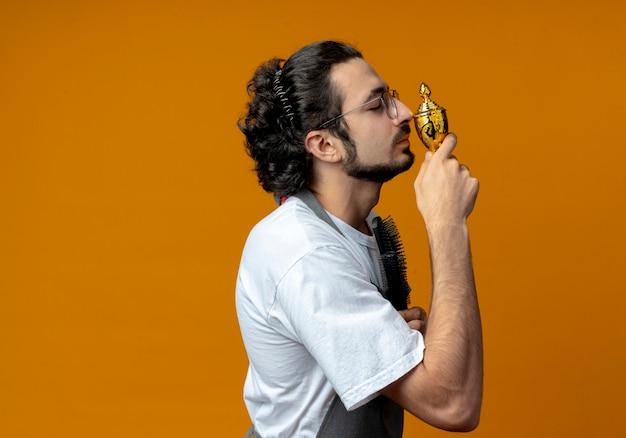 Junger kaukasischer männlicher friseur mit brille und welligem haarband in uniform, der in der profilansicht steht und kämme und siegerpokal mit geschlossenen augen hält holding
