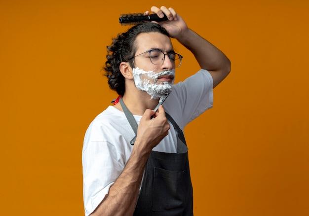 Junger kaukasischer männlicher friseur mit brille und welligem haarband in uniform, der sein haar kämmt und den bart mit einem rasiermesser mit rasierschaum rasiert, der mit geschlossenen augen auf sein gesicht gelegt wird