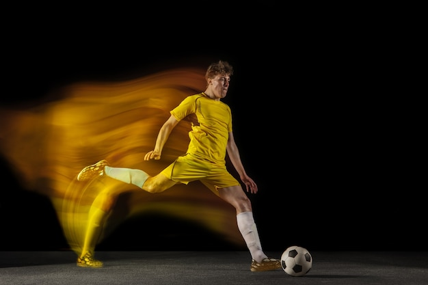 Junger kaukasischer männlicher fußball oder fußballspieler, der ball für das ziel im gemischten licht auf dunklem wandkonzept des professionellen sporthobby des gesunden lebensstils tritt