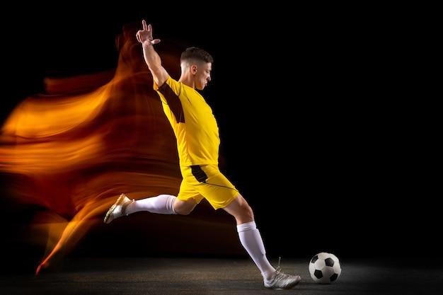 Junger kaukasischer männlicher fußball- oder fußballspieler, der ball für das ziel in gemischtem licht auf dunklem wandkonzept des gesunden lebensstils professionelles sporthobby tritt