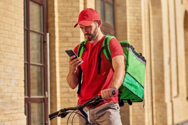 Junger kaukasischer männlicher kurier, der in smartphone schaut