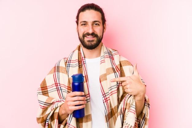 Junger kaukasischer mann an einem kampierenden tag eine thermosflasche halten, die eigenhändig auf einen hemdkopienraum, stolz und überzeugt zeigt