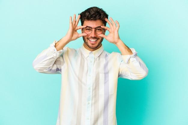 Junger kaukasischer mann auf blauem hintergrund isoliert, der ein okayzeichen über den augen zeigt