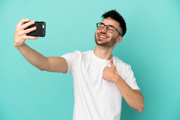 Junger kaukasischer mann auf blauem hintergrund isoliert, der ein selfie mit dem handy macht