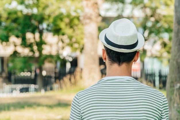 Junger kaukasischer mann auf dem rücken, der in einem park musik hört