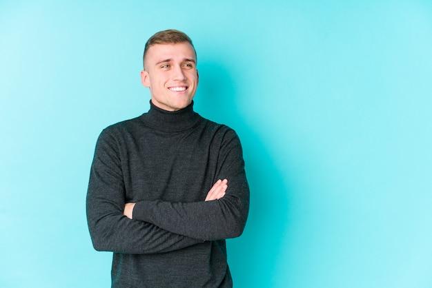 Junger kaukasischer mann auf einer blauen wand, die zuversichtlich mit verschränkten armen lächelt.