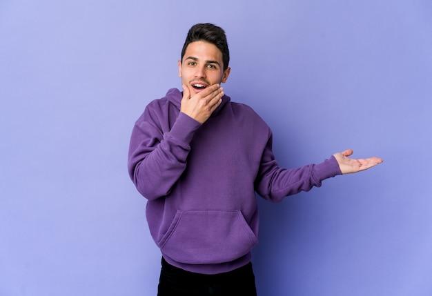 Junger kaukasischer mann auf purpur hält kopienraum auf einer handfläche, hand über wange halten. erstaunt und entzückt.