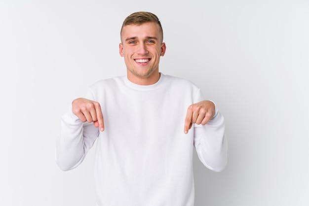 Junger kaukasischer mann auf weiß zeigt mit den fingern nach unten, positives gefühl.